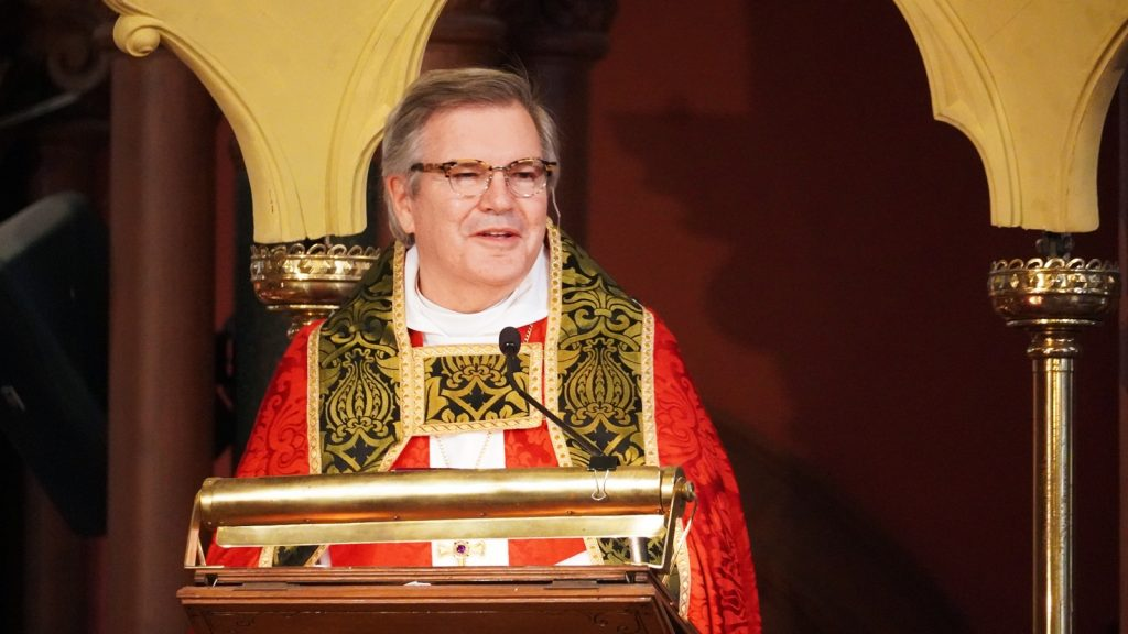 Bishop delivering sermon from pulpit